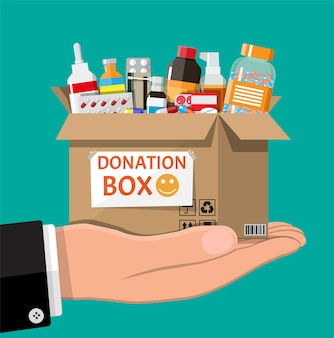 Cardboard box full of drugs in hand. needed items for donation. different pills bottles, healthcare, pharmacy.