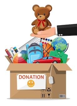 Картонный ящик для пожертвований, полный игрушек, книг, одежды и устройств. помощь детям, поддержка бедных детей. контейнер для пожертвований в руке. социальная забота, волонтерство, концепция благотворительности. плоские векторные иллюстрации