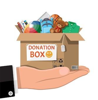 장난감, 책, 옷 및 장치로 가득 찬 골판지 기부 상자. 아이들을 위한 도움, 가난한 아이를 위한 지원. 손에 용기를 기부하십시오. 사회 복지, 자원 봉사, 자선 개념. 평면 벡터 일러스트 레이 션