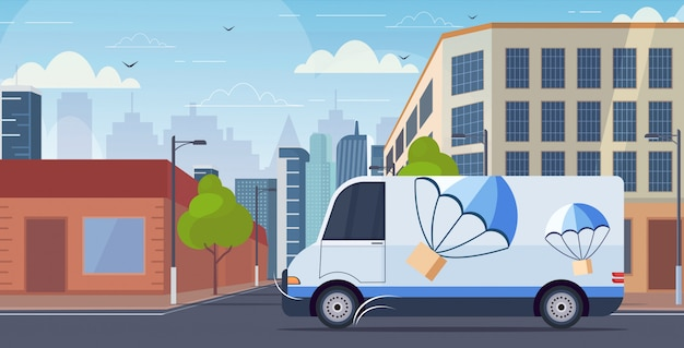 Cargo van truck driving city road parcel box with parachute flying down from sky express delivery service concept modern cityscape background horizontal