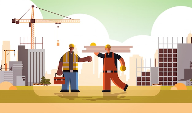 Carpenter holding planks discussing with african american engineer workmen in uniform standing together building concept construction site background flat full length horizontal