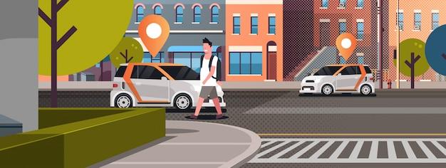 道路に位置ピンが付いている車オンラインでタクシーを注文カーシェアリングのコンセプトカーシェアリングサービスを使用しているモバイル輸送男近代的な都市街並み