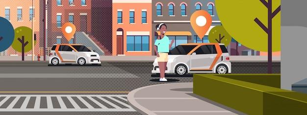 道路にピンを配置した車のオンライン注文タクシーカーシェアリングコンセプトモバイル交通女性カーシェアリングサービスを使用して近代的な都市通り都市景観背景水平