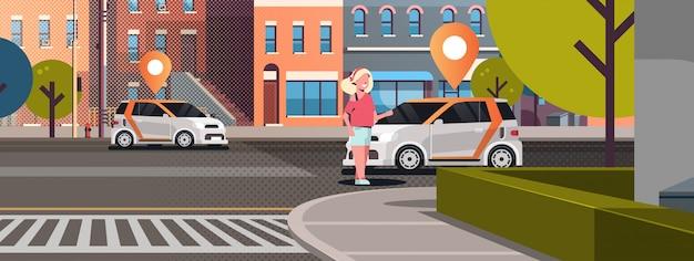 道路上の位置ピンが付いている車オンラインでタクシーを注文カーシェアリングのコンセプトカーシェアリングサービスを使用しているモバイル輸送の女性近代的な都市の街並み