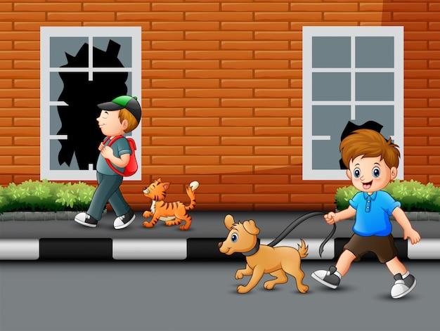 彼のペットと一緒に道を歩いている少年を漫画します。