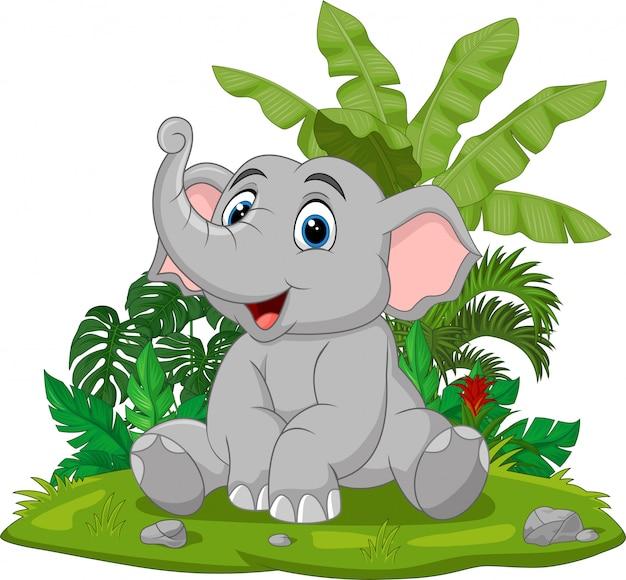 Мультяшный слоненок сидит в траве