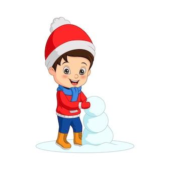 雪だるまを構築する冬服の漫画の少年