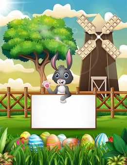 Cartoon bunny waving hand with blank sign in the farm