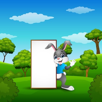 Cartoon bunny waving hand with blank sign in the park
