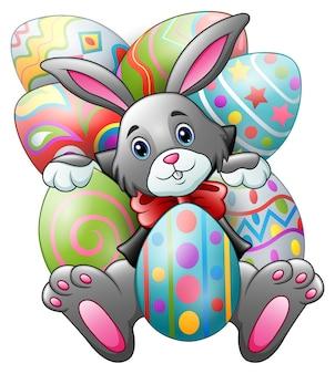 Мультяшный кролик с большими пасхальными яйцами на белом фоне