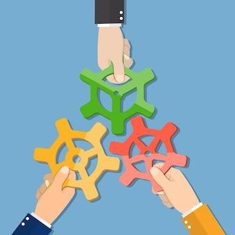 漫画のビジネスマンの手がギアを結合します。ビジネスチームとチームワークの概念。