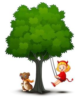 Девочка-мультфильм-дьявол и собака играют под деревом