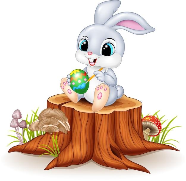 Cartoon easter bunny painting an egg on tree stump