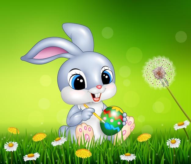 Cartoon easter bunny painting an egg