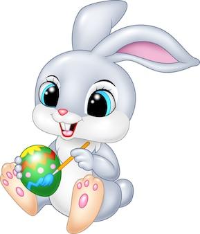 Cartoon funny easter bunny painting an egg
