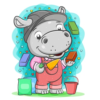 The cartoon of the grey builder hippopotamus hold brick with cement spoon