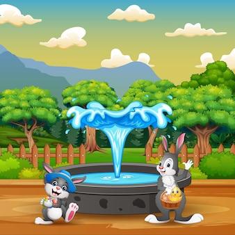 噴水の近くに立っている漫画の幸せなウサギ