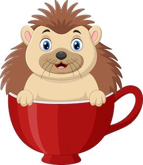Мультяшный счастливый ежик сидит в красной чашке