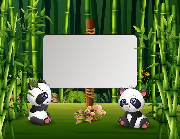 緑の野原に座っている2匹のパンダの漫画イラスト