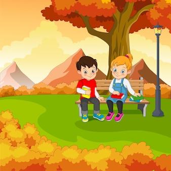 秋の公園の木の下で本とベンチに座っている漫画の子供たち