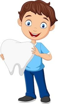 Cartoon little boy holding big tooth