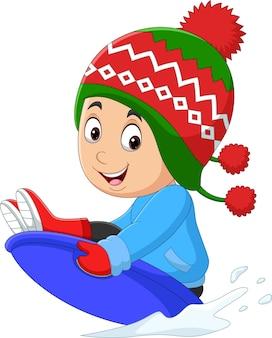 漫画の小さな男の子が丘をそり滑ります