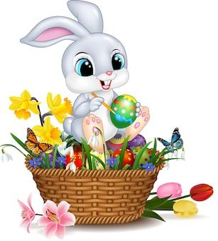 Cartoon little rabbit painting an easter egg