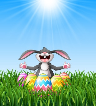Cartoon rabbit laughing with easter eggs in the grass