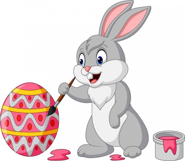 Мультяшный кролик рисует пасхальное яйцо