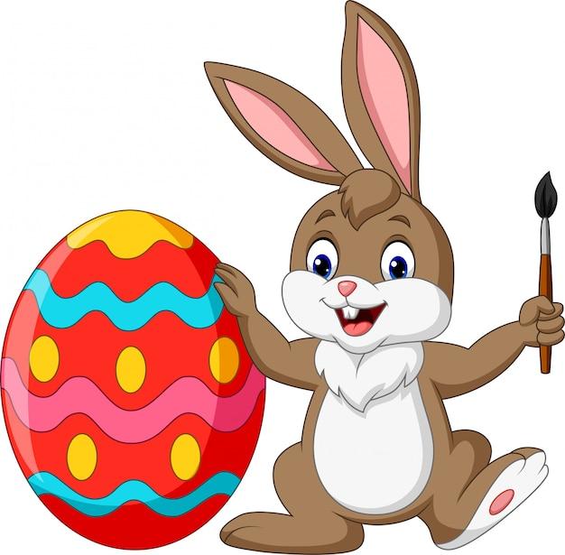 Cartoon rabbit painting an easter egg