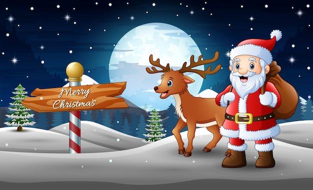 漫画のサンタクロースと鹿は贈り物の袋で雪の中に立って