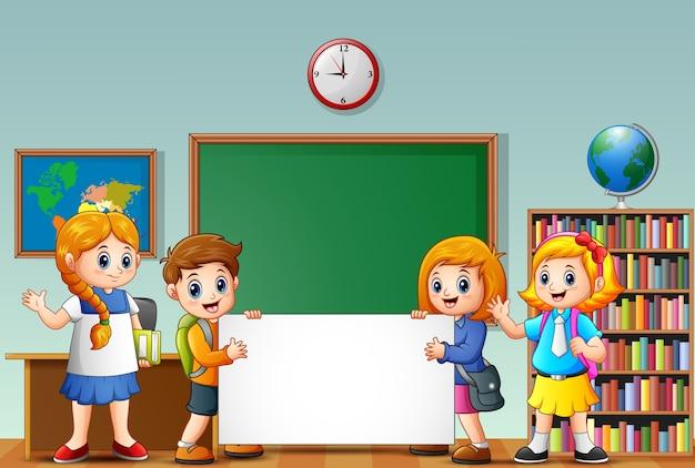 教室で空白のサインを持つ漫画の学校の子供たち