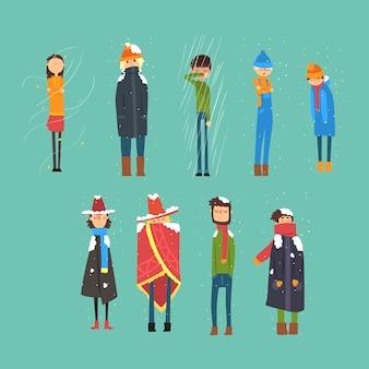 남자와 여자 밖에 서 얼어의 만화 세트. 춥고 눈이 내리고 비가 오는 날씨. 모직 모자, 겨울 코트, 따뜻한 판초, 스카프 및 스웨터를 입은 사람들 캐릭터. 삽화.