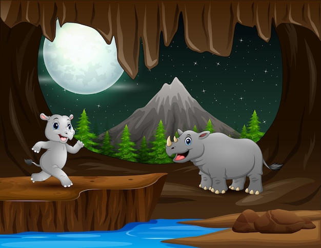 暗い洞窟のイラストに住んでいる2頭のサイを漫画