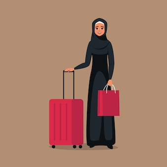 Cartoon young arab woman stands with luggage for travel. isolated from background Premium Vector