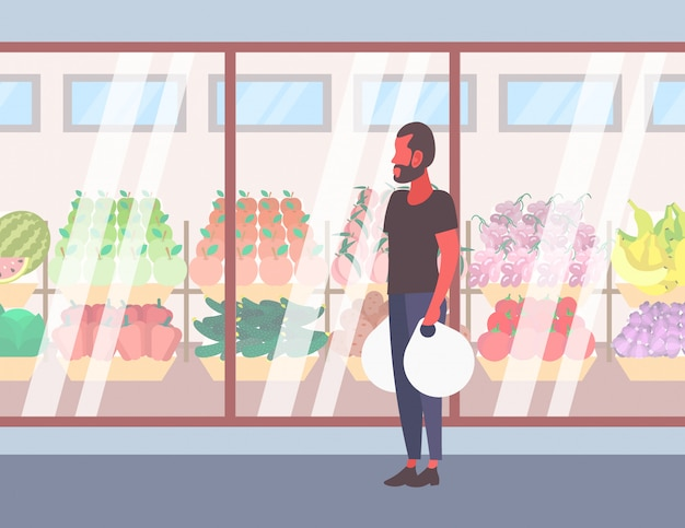 Casual man holding shopping bags walking in front of fresh organic fruits vegetables modern supermarket shop glass window guy customer full length cartoon character flat