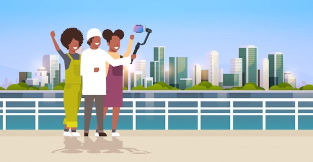 Casual people using 3-axis gimbal stabilizer selfie stick for smartphone happy   tourists taking photo standing together over cityscape background horizontal full length