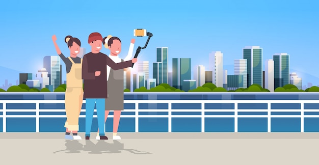 Casual people using  gimbal stabilizer selfie stick for smartphone happy tourists taking photo standing together over cityscape background horizontal full length