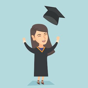 Caucasian graduate throwing up graduation hat.