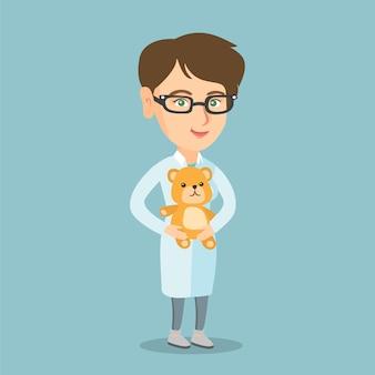 Caucasian pediatrician doctor holding a teddy bear