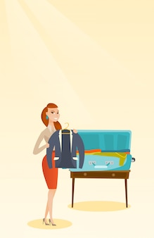 Caucasian woman packing clothes in a suitcase