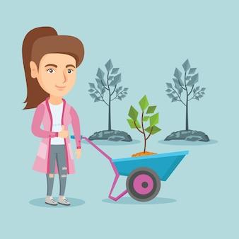 Caucasian woman pushing wheelbarrow with plant.