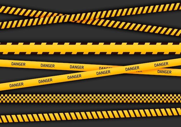 黄色と黒色の注意と危険のテープ。警察の注意線または建設中のリボン、白い背景で隔離の警告標識コレクション。