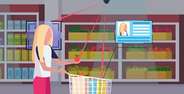 食料品の識別の顔の認識の概念の保安用カメラの監視cctvシステムの食料品店のスーパーマーケットの内部の肖像画の横のショッピングトロリーカートを押す女の子