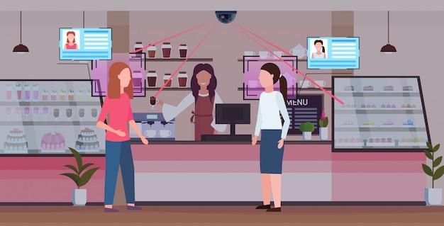 女性の訪問者を識別する女性のバリスタのコーヒーショップの労働者識別顔認識コンセプトセキュリティカメラ監視cctvシステムモダンなカフェテリアインテリア全長水平