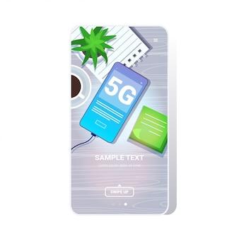 デスクトップ上の携帯電話5gオンライン通信ネットワークワイヤレスシステム接続コンセプト第5世代の高速インターネットトップアングルビュースマートフォンスクリーンモバイルアプリ