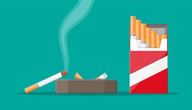 Керамическая пепельница, полная дымящихся сигарет. посуда для копчения. пакет сигаретной бумаги. нездоровый образ жизни.