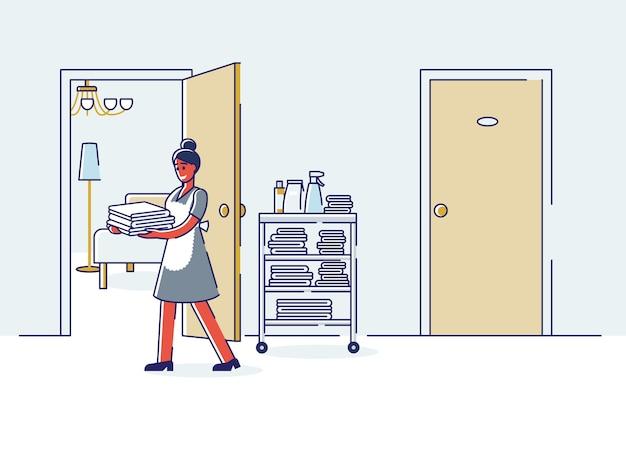 Горничная держит чистые полотенца в коридоре отеля. Premium векторы