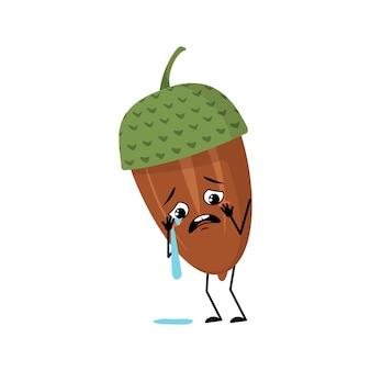 울고 눈물을 흘리는 감정, 슬픈 얼굴, 우울한 눈, 팔, 다리를 가진 캐릭터 도토리. 우울한 숲 식물, 가을 너트