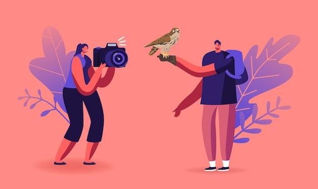 Персонажи фестиваля соколиной охоты или открытого зоопарка. женщина фотографирует дикого сокола, сидящего на руке человека в кожаной перчатке